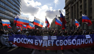 epa05183632 People participate with a banner 'Russia will be free' during a memorial march for Boris Nemtsov to mark the murder's first anniversary, in Moscow, Russia, 27 February 2016. Boris Nemtsov, liberal opposition leader and sharp critic of president Putin, was killed on 27 February 2015 by a group of Chechen military servicemen. Five were arrested, one was killed during detention, and one of organizers is still wanted.  EPA/YURI KOCHETKOV